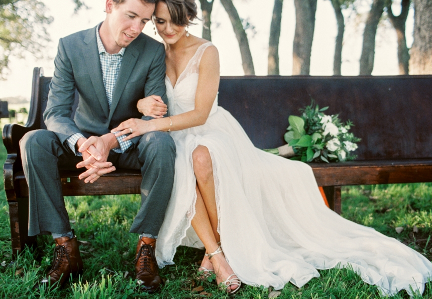 bride and groom sitting on church pew under grove of trees with gorgeous wedding dress